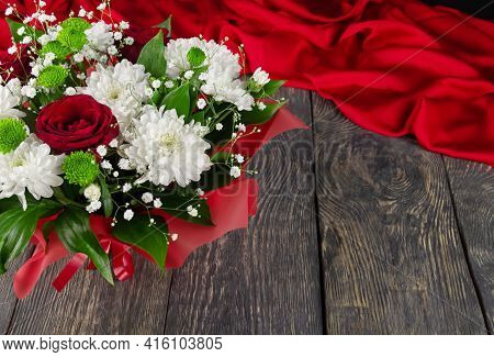 Bright Bouquet Of Roses And White Chrysanthemums On A Wooden Background And Scarlet Fabric