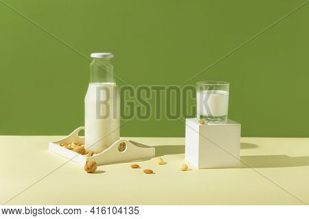 Glass With Vegan Milk From Various Nuts With A Bottle On White Wooden Tray On Sunlit Background. Dai