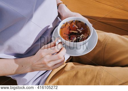White Cup Of Herbal Tea With A Saucer In Female Hands. The Concept Of Tea Drinking, Healthy Drinks.