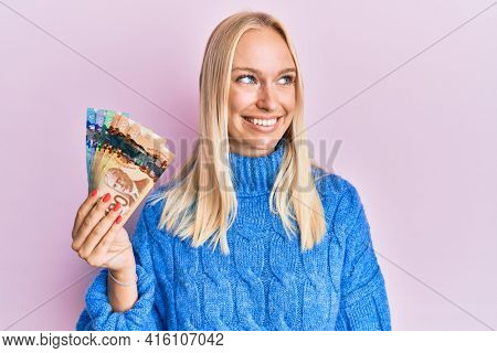 Young blonde girl holding canadian dollars smiling looking to the side and staring away thinking.