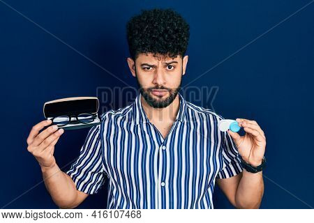Young arab man with beard holding glasses and contact lenses skeptic and nervous, frowning upset because of problem. negative person.