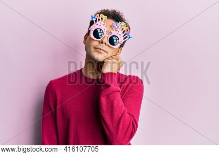 Handsome hispanic man wearing funny happy birthday glasses thinking concentrated about doubt with finger on chin and looking up wondering