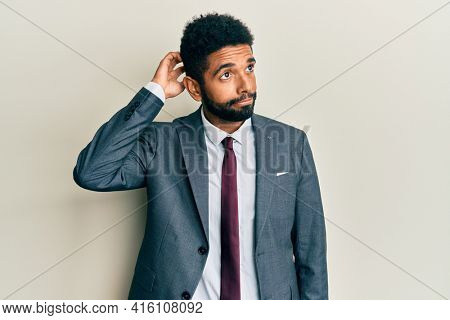 Handsome hispanic man with beard wearing business suit and tie confuse and wondering about question. uncertain with doubt, thinking with hand on head. pensive concept.