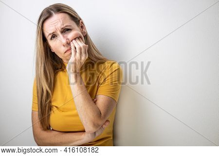 Mid-aged woman touching her mouth with painful expression because of a dental issue