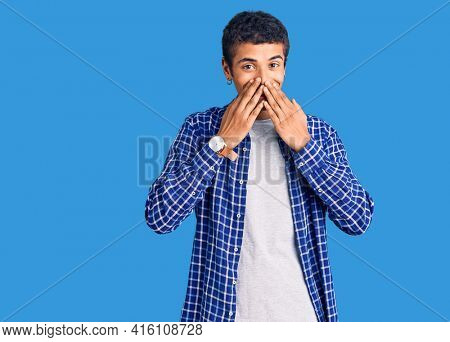 Young african amercian man wearing casual clothes laughing and embarrassed giggle covering mouth with hands, gossip and scandal concept