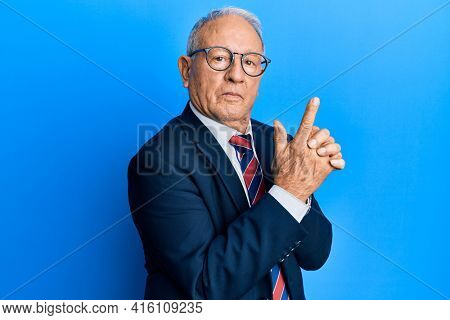 Senior caucasian man wearing business suit and tie holding symbolic gun with hand gesture, playing killing shooting weapons, angry face