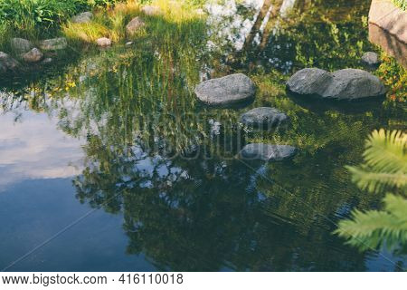 Pond Water Stones Landscape Wet Stones By Mood Lake Shore. Sky In Reflection. Beautiful Small Garden