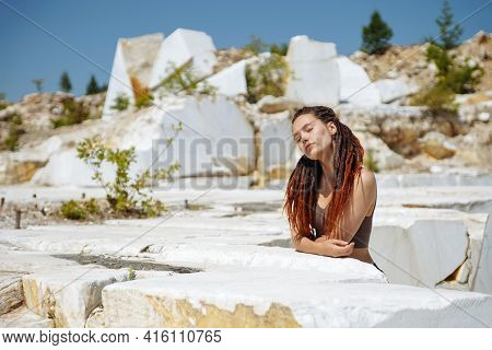 Girl With Dreadlocks Rests In Marble Quarry With Eyes Closed. Natural Source Of Marble. Human And Na