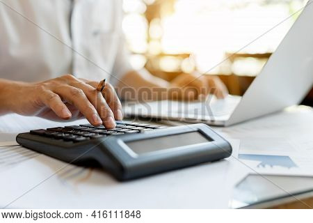 Close Up Businessman Pressing On Calculator For Calculating Cost Estimating With Laptop.