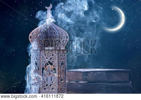 Arabic lantern with with Holy Quran and crescent moon. Festive greeting card for Muslim holy month Ramadan Kareem.