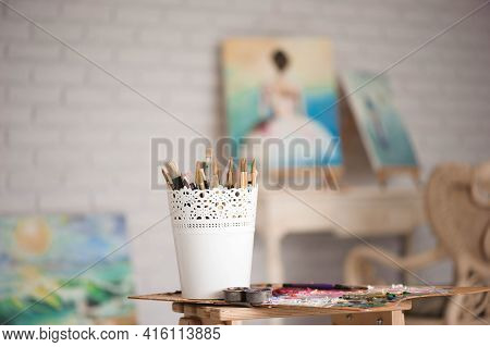 Artistic Equipment: Easel, Paint Brushes, Tubes Of Paint, Palette And Paintings On Work Table In A A