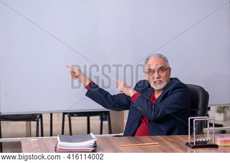 Old teacher physicist sitting in the classroom