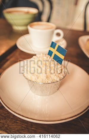 Swedish Traditional Creamy Brownie On A Plate On A Wooden Table. Swedish Flags. Coffee Break Concept