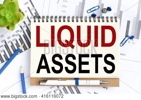 Liquid Assets. Text On White Notepad Paper On A Light Background Near Financial Charts