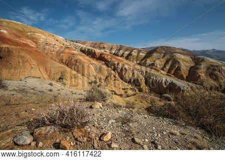 Large Hills Of Red And Yellow Clay, Traces Of Erosion, Rocky Surface And Sparse Vegetation. Martian