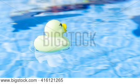 Funny Rubber Ducky. Yellow Inflatable Toy For Kids Swim In Blue Water Of Summer Pool. Minimal Summer