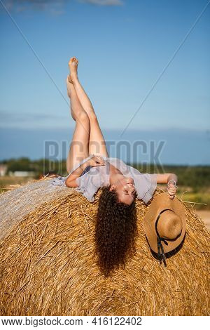 Attractive Woman Posing In The Mown Wheat Fields With Sheaf And Sky In The Village. Hay Bales In The