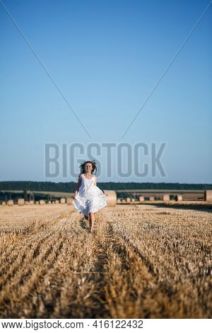A Young Beautiful Woman In A White Summer Dress Stands On A Mown Wheat Field With Huge Sheaves Of Ha