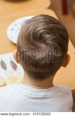 The Back Of A Boys Head With Curled Hair On Top. Close-up Of A Hairstyle On A Childs Head. Back View