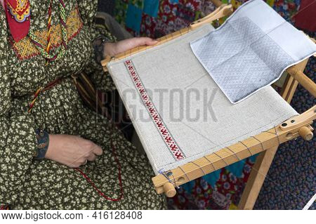 Woman Makes Cloth On An Old Loom. Festival Of Historical Reconstruction. Clothing Weaving Process.