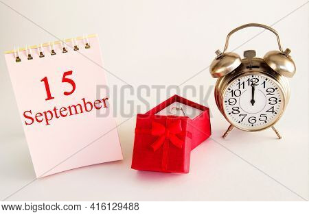 Calendar Date On Light Background With Red Gift Box With Ring And Alarm Clock With Copy Space. Septe
