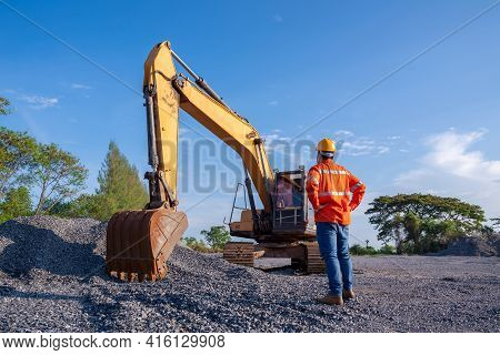 Driver Excavator For Road Construction, Crawler Excavator In Construction Site On Blue Sky Backgroun