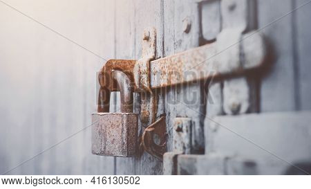 An Old Metal Large Lock Hangs On A Vintage Wooden Gray Gate With A Rusty Latch, Illuminated By Light