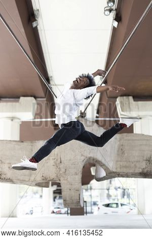 African American Male Dancer Performing Acrobatic Jump In The City Outdoors. Urban Dance Concept. Sp