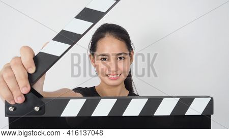 Asian Young Woman Holding Black Clapper Board Or Movie Slate Or Clapperboard .it Use In Video Produc