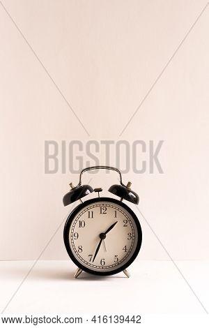 Retro Alarm Clock On Wooden Table. Black Background