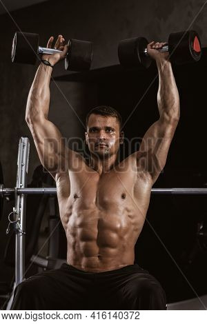 Fitness in gym, sport and healthy lifestyle concept. Handsome athletic man with naked torso making exercises. Bodybuilder male model training muscles lifting large dumbbells up.