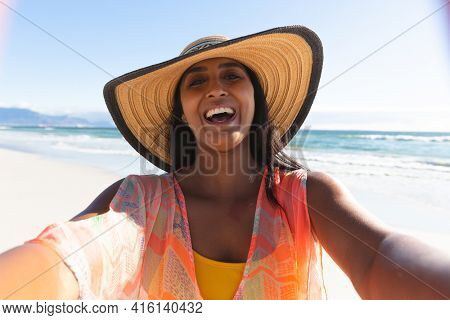 Happy mixed race woman on beach holiday taking selfie. outdoor leisure vacation time by the sea.