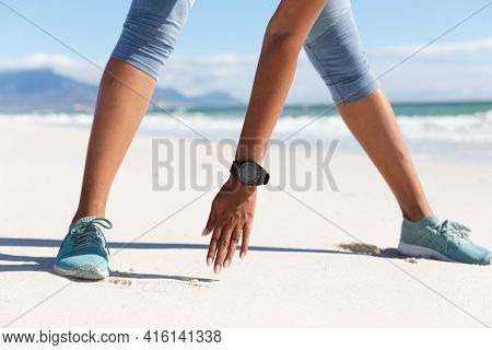 Low section of mixed race woman exercising on beach wearing smartwatch stretching. healthy outdoor leisure time by the sea.