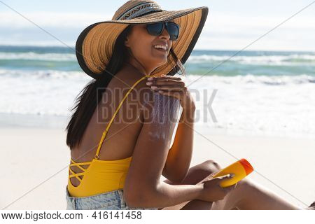 Smiling mixed race woman on beach holiday using sunscreen cream. healthy outdoor leisure time by the sea.