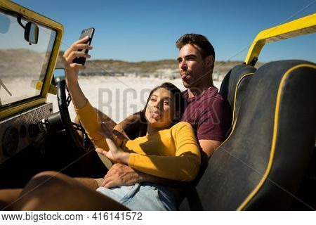 Caucasian couple on a beach buggy by the sea taking selfie. beach break on summer holiday road trip.