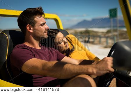 Happy caucasian couple sitting in beach buggy by the sea relaxing. beach break on summer holiday road trip.