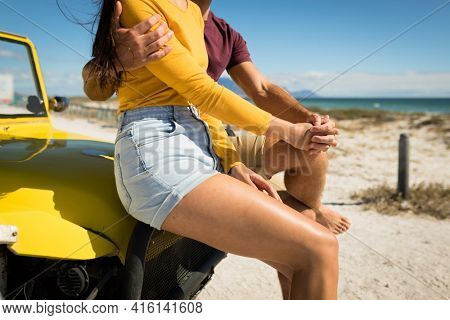 Midsection of happy caucasian couple sitting on beach buggy by the sea holding hands. beach break on summer holiday road trip.
