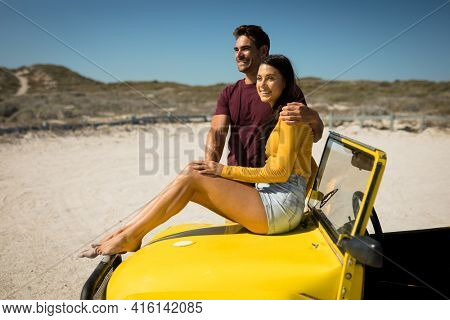 Happy caucasian couple, man embracing woman sitting on beach buggy by the sea. beach break on summer holiday road trip.