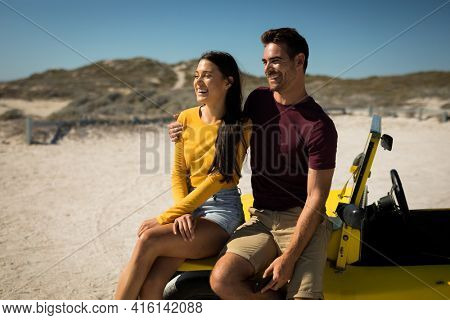 Happy caucasian couple sitting on beach buggy by the sea smiling. beach break on summer holiday road trip.