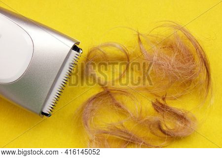 Haircut Machine Is Insulated On A Yellow Background, Next To A Strand Of Trimmed Hair. Hair. Hairdre