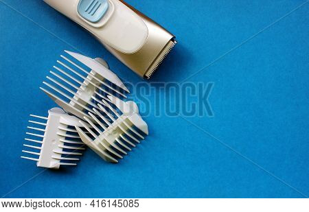 The Haircut Machine Is Insulated On A Blue Background With Haircut Attachments. Hair. A Hairdresser