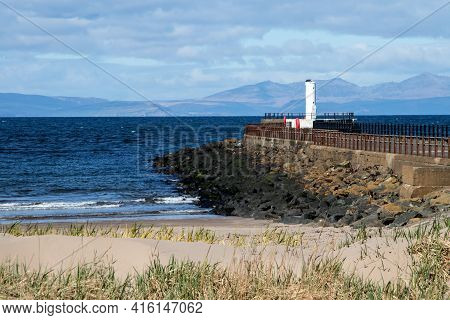 View Of Isle Of Arran Scotland From Ayr Beach With Jetty And Harbour Light