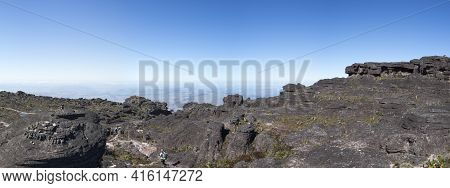 Landscape At The Top Of Mount Roraima In The Morning With Blue Sky. Unrecognizable Hiker Walking Thr