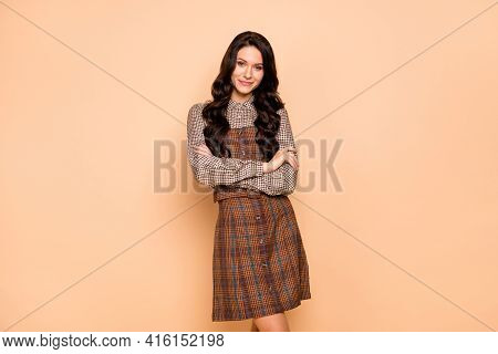 Portrait Of Attractive Cheery Wavy-haired Girl Wearing Checked Garment Folded Arms Isolated On Beige