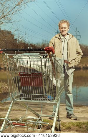 Older Beggar Man With His Property In Shopping Cart