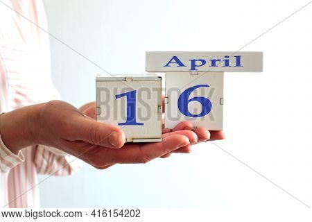 Calendar For April 16 : Women's Hands Hold Cubes With The Number 16, The Name Of The Month Of April