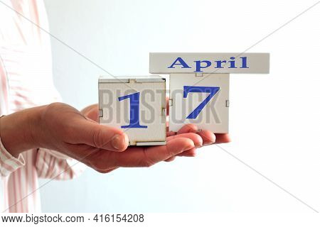 Calendar For April 17 : Women's Hands Hold Cubes With The Number 17, The Name Of The Month Of April