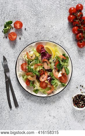 Mix Salad With Tomatoes And Grilled Shrimps With Sauce And Clematis On The Kitchen Table. View From
