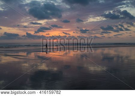 Sunset View At The Beach Of Matapalo With Silhouette Of Man Making His Jogging, Costa Rica. Matapalo