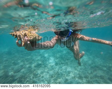 Woman Doing Snorkeling With Mask Underwater With Seashell. Concept Of Healthy Lifestyle And Leisure.